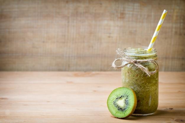 Gesunder grüner smoothie in einem glas auf altem holz.