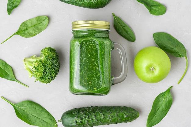 Gesunder grüner smoothie in einem glas zum mitnehmen aus spinat, brokkoli, avocado, apfel und gurke. draufsicht. flach liegen. rohes veganes lebensmittelkonzept