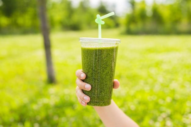 Gesunder grüner smoothie in einem glasbecher mit spinat, kiwi, banane und apfel