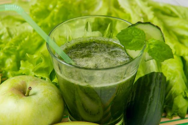Gesunder grüner smoothie mit bestandteilen auf holz