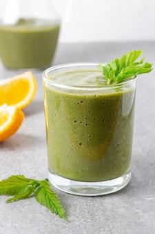 Gesunder grüner smoothie mit brennnesseln auf grauem tisch