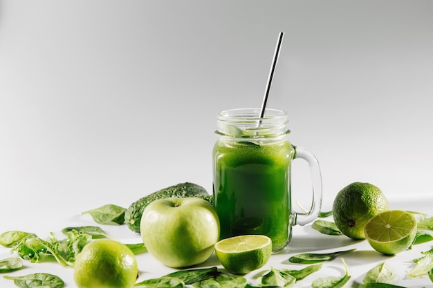 Gesunder grüner smoothie mit spinat und grünem obst und gemüse auf weißem tisch