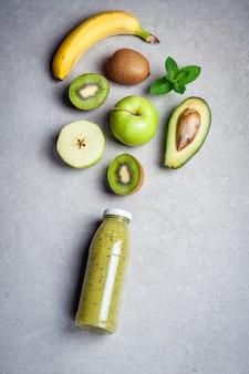 Gesunder grüner smoothie und bestandteile auf grauem hintergrund