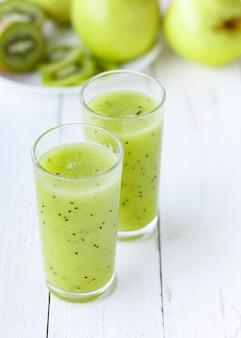Gesunder grüner smoothieapfel und -kiwi auf weißer tabelle