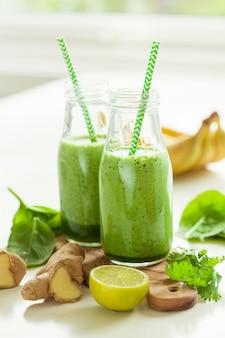 Gesunder grüner spinat-smoothie mit koriander-limetten-bananen-ingwer