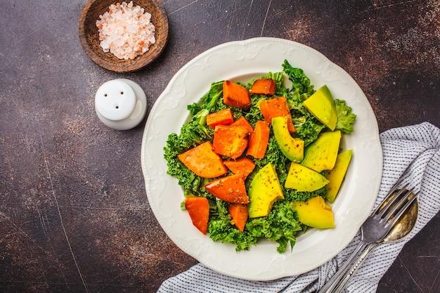 Gesunder grünkohlsalat mit avocado und gebackenen süßkartoffeln.