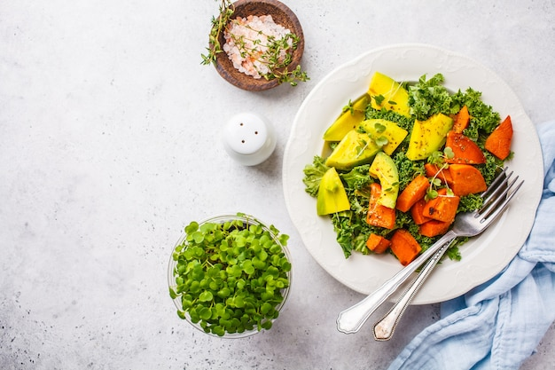 Gesunder grünkohlsalat mit avocado und gebackener süßkartoffel