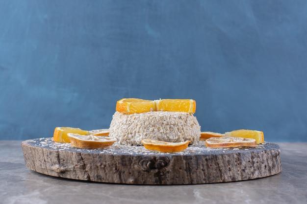 Gesunder haferbrei mit orangenscheiben auf einem holzstück.