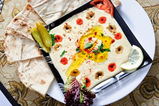 Gesunder hausgemachter cremiger hummus mit olivenöl und pita-chips.
