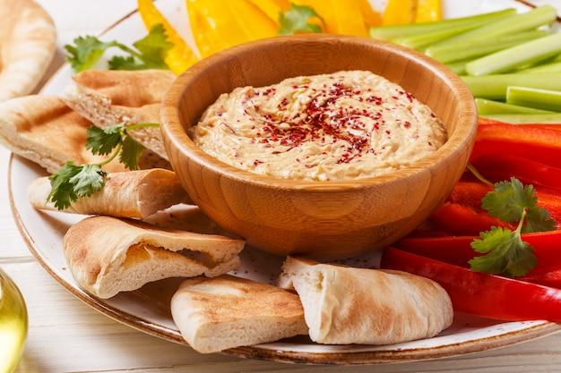 Gesunder hausgemachter hummus mit verschiedenem frischem gemüse und fladenbrot.