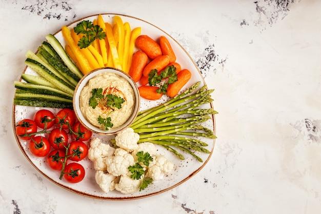Gesunder hausgemachter hummus mit verschiedenem frischem gemüse.