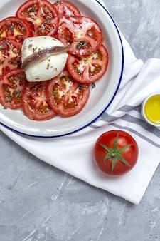 Gesunder hausgemachter tomatensalat mit mozzarella, sardellen und oregano