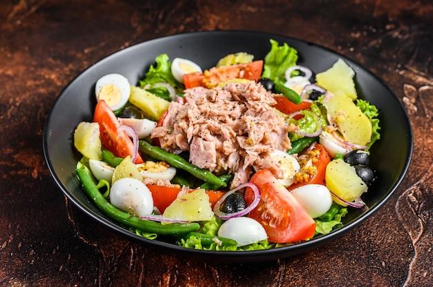 Gesunder herzhafter salat mit thunfisch, grünen bohnen, tomaten, eiern, kartoffeln und schwarzen oliven auf einem teller. dunkler hintergrund. draufsicht.