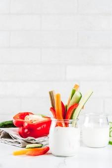Gesunder imbißaperitif des sommers, sortierte bunte frischgemüsestöcke (sellerie, rhabarber, pfeffer, gurke und karotte) mit jogurtsoßenbad
