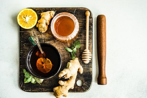 Gesunder ingwertee mit zitrone und honig auf rustikalem