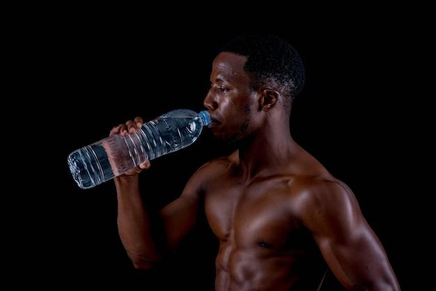 Gesunder junger afrikanischer mann, der glas wasser halten ausübt. auf einem schwarzen hintergrund.