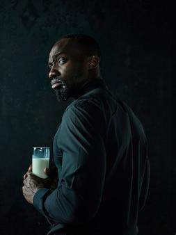 Gesunder junger afrikanischer mann holging tasse milch auf einem schwarzen studio.