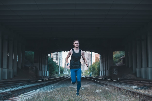 Gesunder junger mann, der in der stadt nachts rüttelt. männlicher athlet, der unter brücke entlang den eisenbahn-lkws läuft.