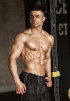 Gesunder junger mann, der stark in der turnhalle steht und muskeln biegt