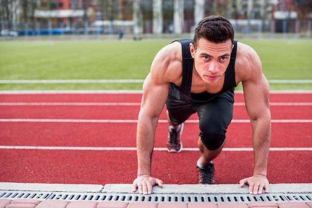 Gesunder junger mann des muskulösen sitzes, der liegestütz auf rennstrecke tut