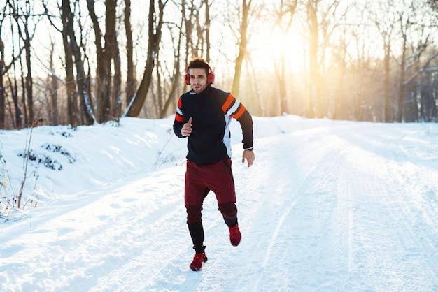 Gesunder junger mann in sportbekleidung mit kopfhörern, die auf schneebedeckter winterstraße am morgen laufen.
