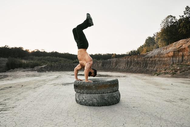 Gesunder junger mann mit athletischem körper, der zwei schwere reifen für sportaktivität an sandgrube verwendet. muskulöser hemdloser mann, der schwarze fleckhose und schützende gesichtsmaske trägt.