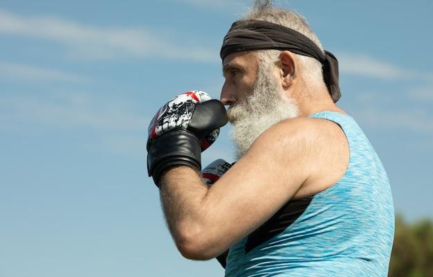 Gesunder kämpfer bärtiger älterer alter mann boxhandschuhe.
