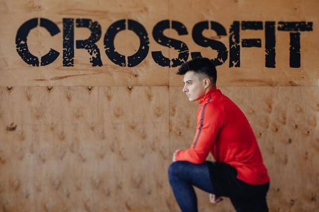 Gesunder kerl im hintergrund der aufschrift crossfit, thema der gesundheit