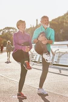 Gesunder körper in voller länge schuss von reifem mann und frau in sportkleidung lächelnd beine strecken, während