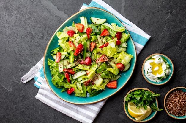 Gesunder kopfsalaterdbeersalat mit leinsamen auf blauer platte