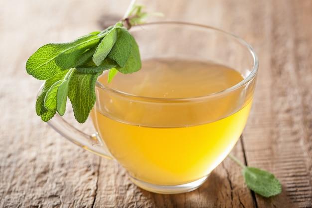 Gesunder kräuter-salbei-tee mit grünem blatt in der glasschale