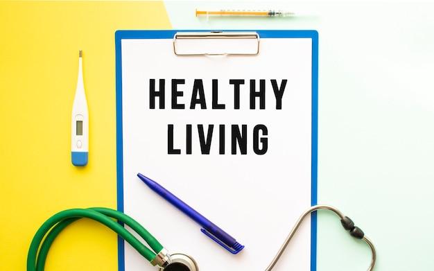Gesunder lebendiger text auf einem briefkopf in einem medizinischen ordner auf einem schönen hintergrund. stethoskop, thermometer und stift.