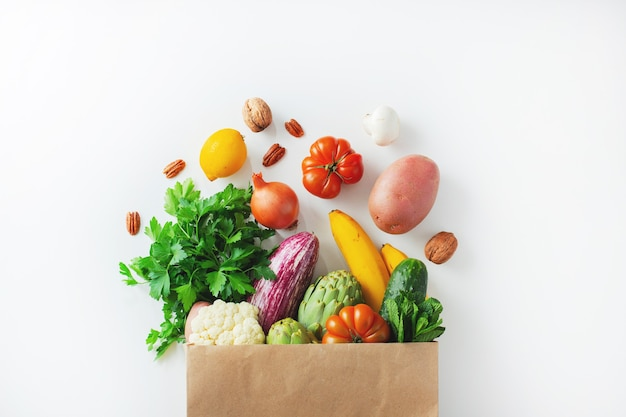 Gesunder lebensmittelhintergrund. gesundes veganes vegetarisches essen in papiertütengemüse und -obst auf weiß, kopienraum. einkaufen lebensmittelsupermarkt und sauberes veganes esskonzept.
