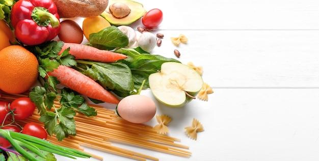 Gesunder lebensmittelhintergrund. verschiedene obst und gemüse der lebensmittelfotografie auf weißem holztischhintergrund. platz kopieren. der lebensmitteleinkauf.