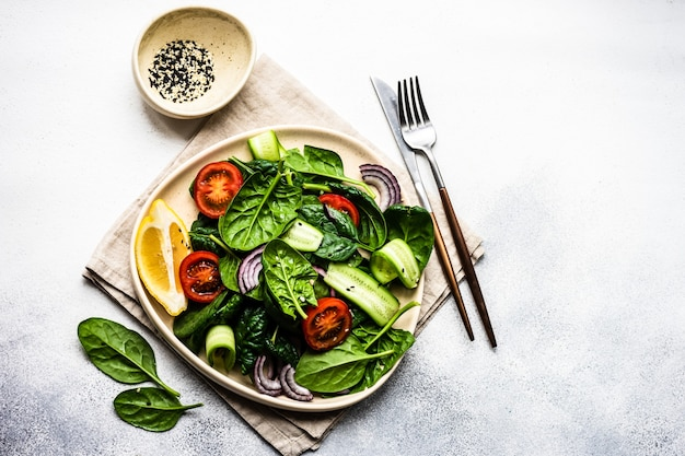 Gesunder lebensmittelsalat mit frischen bio-spinatblättern mit sesam