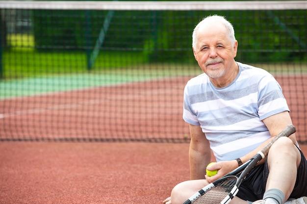 Gesunder lebensstil, älterer mann, rentner, der tennis auf dem platz spielt, sportkonzept