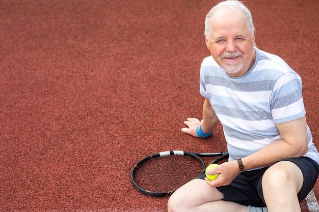Gesunder lebensstil, älterer mann, rentner, der tennis auf dem platz spielt