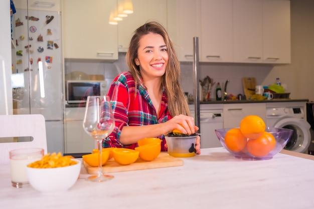 Gesunder lebensstil, blonde kaukasische frau, die orangen für frühstück drückt, das frischen orangensaft macht