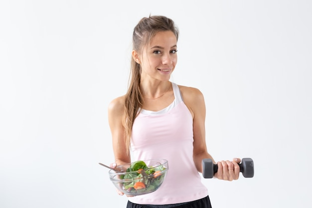 Gesunder lebensstil, ernährung, fitness und menschenkonzept - junge frau isst einen salat und macht sport mit hantel auf weißem hintergrund mit kopienraum.
