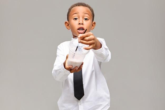 Gesunder lebensstil, essen, trinken und kindheitskonzept. bild des emotional aufgeregten afroamerikanischen schuljungen in der uniform, die plastikglas mit fruchtmilchshake hält und ihnen anbietet, etwas zu haben