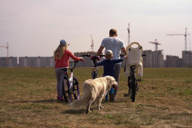 Gesunder lebensstil - familie mit fahrrädern und einem hund, der entlang das feld nahe der stadt geht