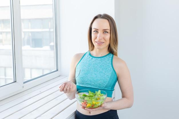 Gesunder lebensstil, fitness- und diätkonzept - diätsalat und schlanke frau in sportkleidung in der nähe von fenster