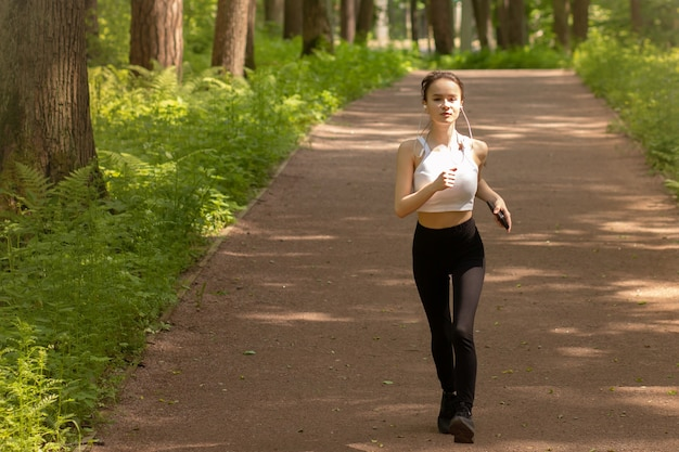 Gesunder lebensstil. junges mädchen in kopfhörern macht sport, rennt