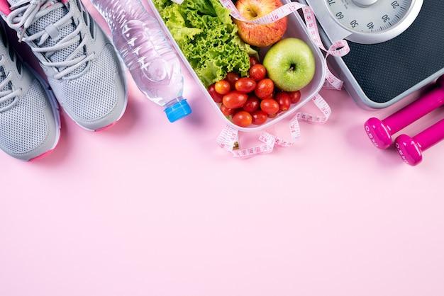 Gesunder lebensstil, lebensmittel und sport auf rosa pastellhintergrund.