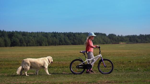 Gesunder lebensstil - mädchen mit einem fahrrad und einem hund, die auf ein feld nahe der stadt gehen