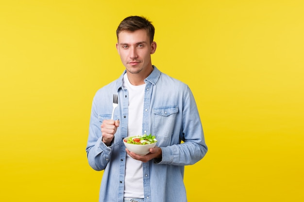 Gesunder lebensstil, menschen und lebensmittelkonzept. frecher, gut aussehender blonder mann, der salat isst, schielt und lächelt erfreut, veganes frühstück kocht, stehend erfreut auf gelbem hintergrund