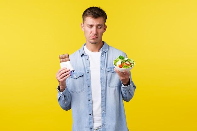 Gesunder lebensstil, menschen und lebensmittelkonzept. unzufriedener und widerstrebender hübscher trauriger kerl will schokoriegel essen und mit ekel auf schüssel mit salat schauen, auf diät sitzen, gelber hintergrund stehen.