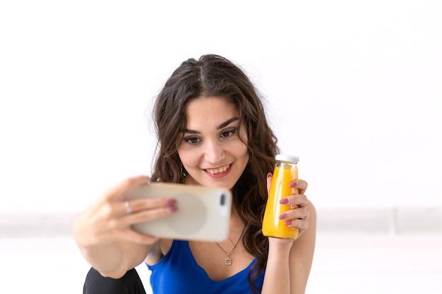 Gesunder lebensstil, menschen und sportkonzept - frau, die selfie nimmt und saft hält