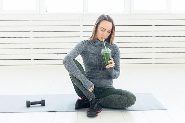 Gesunder lebensstil, menschen und sportkonzept - frau mit gesundem safttrinken für sport