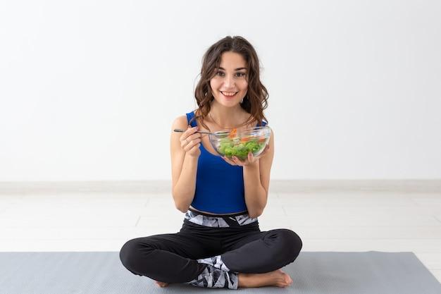 Gesunder lebensstil, menschen und sportkonzept - yoga-frau mit einer schüssel gemüsesalat